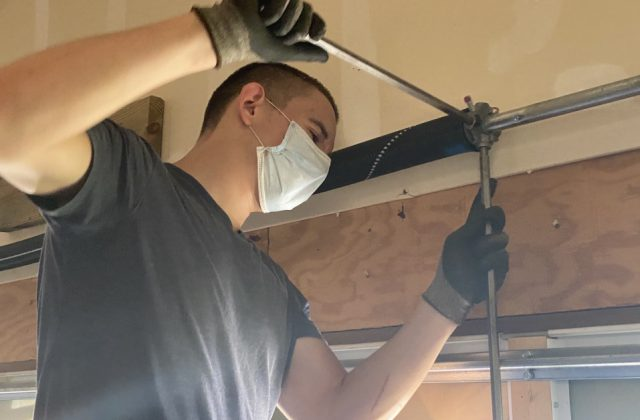 garage-door-repairman-wearing-mask-while-working-on-garage-door-spring